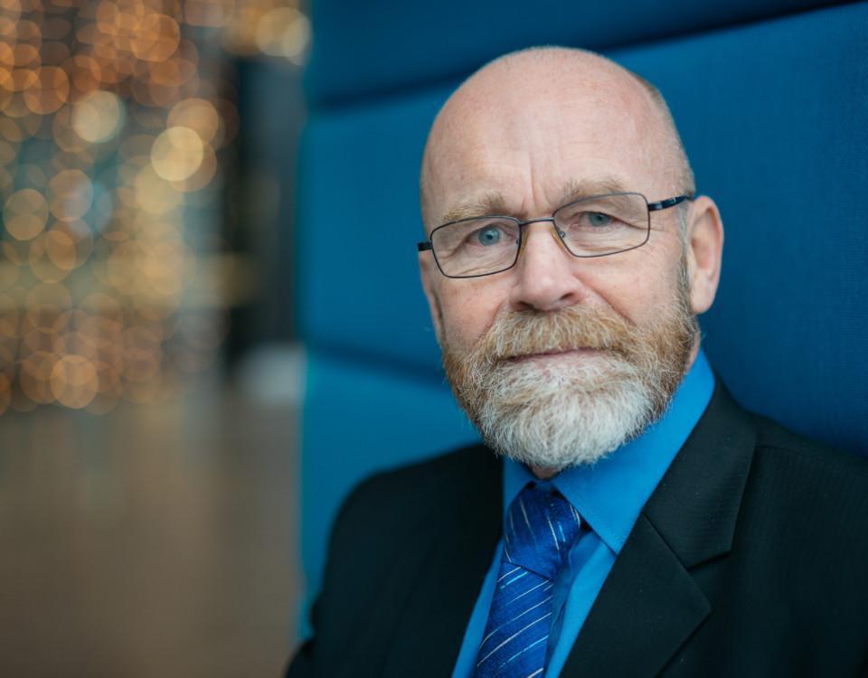 en man med vitt skägg och glasögon iklädd en blå slips