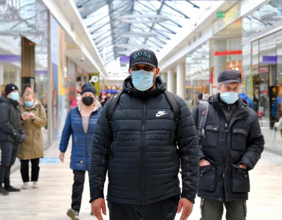 en man med munskydd i ett köpcenter