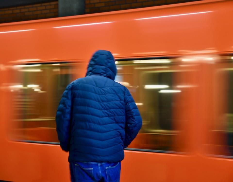 en person med blå jacka står vid en orange metro som rör sig snabbt