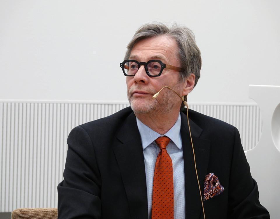 en man med slips och kavaj sitter med en mikrofon