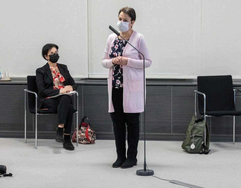 en kvinna i munskydd framför en mikrofon