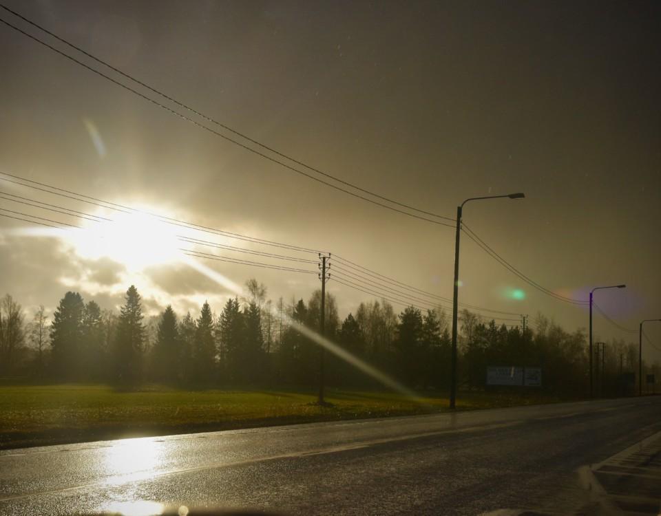 solen skiner igenom molnen på en regning landsväg