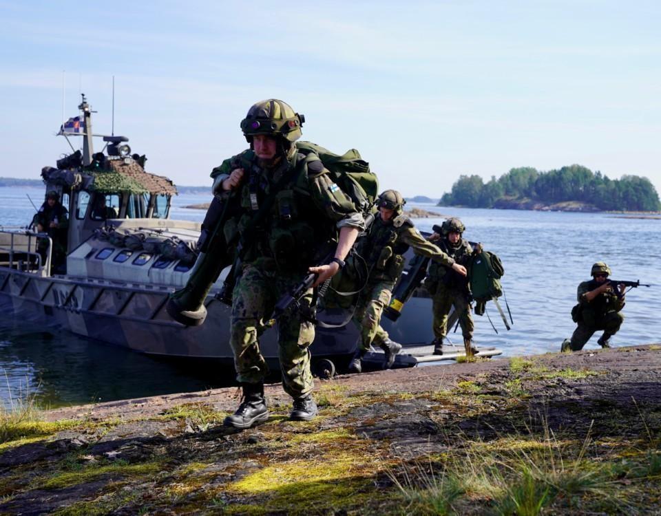 Militärklädda människor vid en båt.