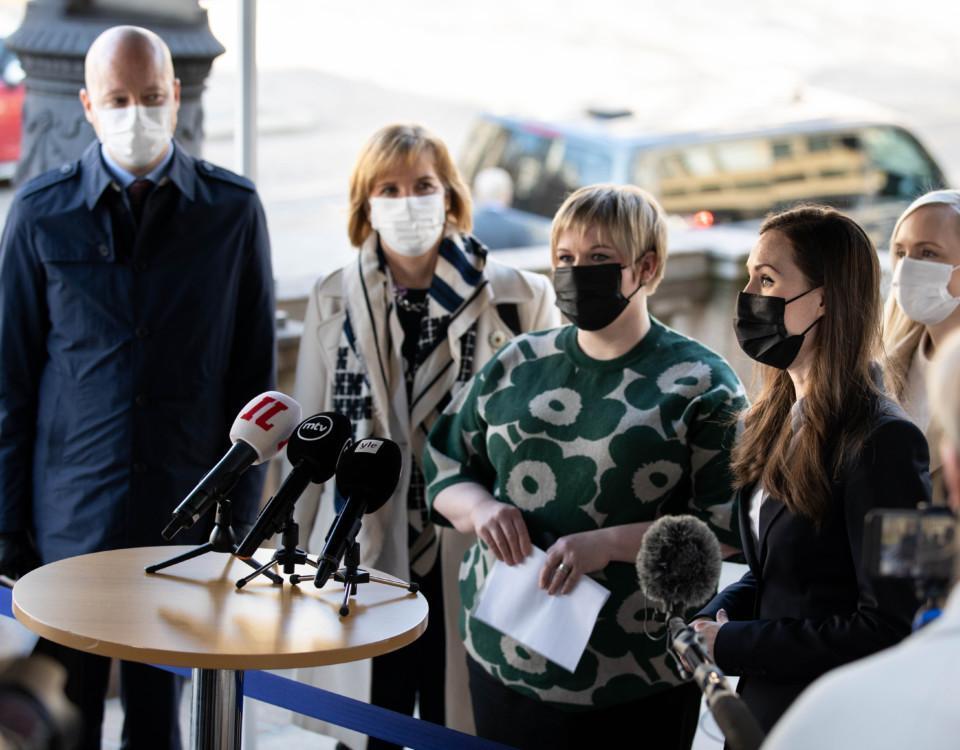 Fyra personer med munskydd vid ett bord med mikrofoner.