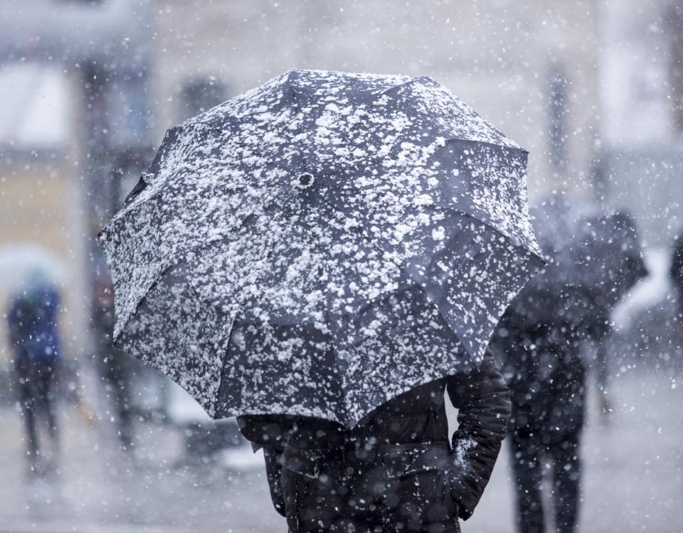 Någon som går med ett paraply i snöfall.
