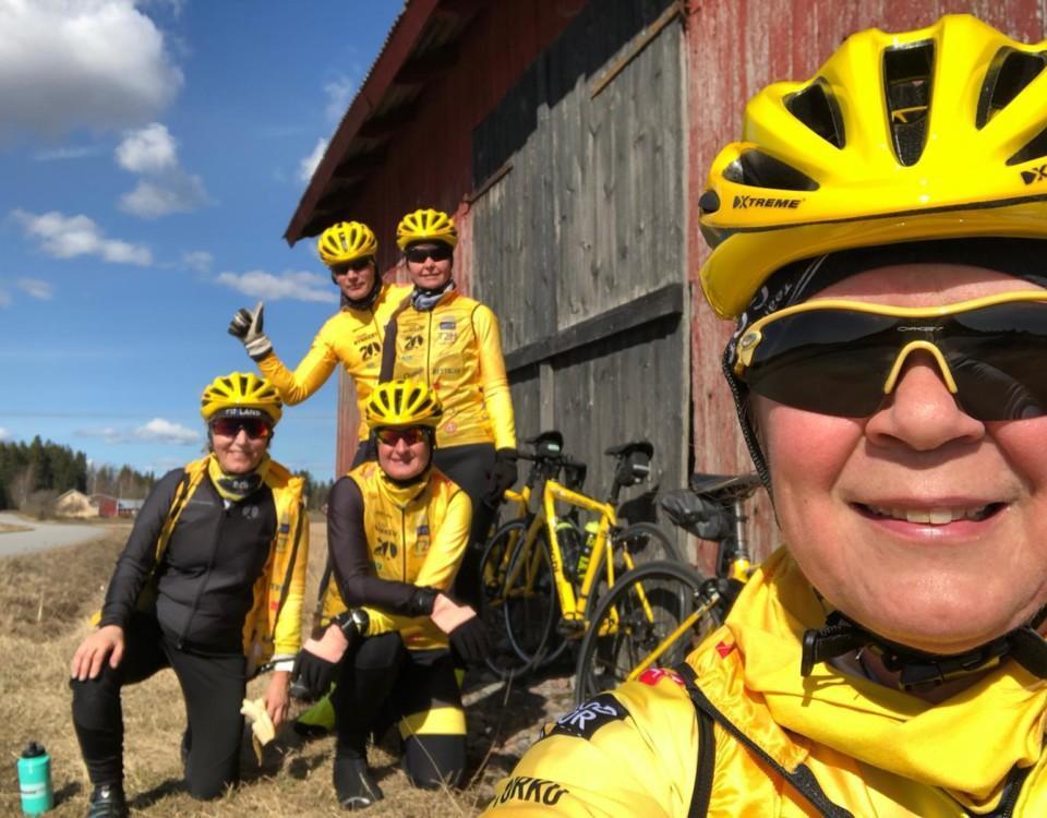 gulklädda människor poserar vid en lada, de har cykelhjälmar