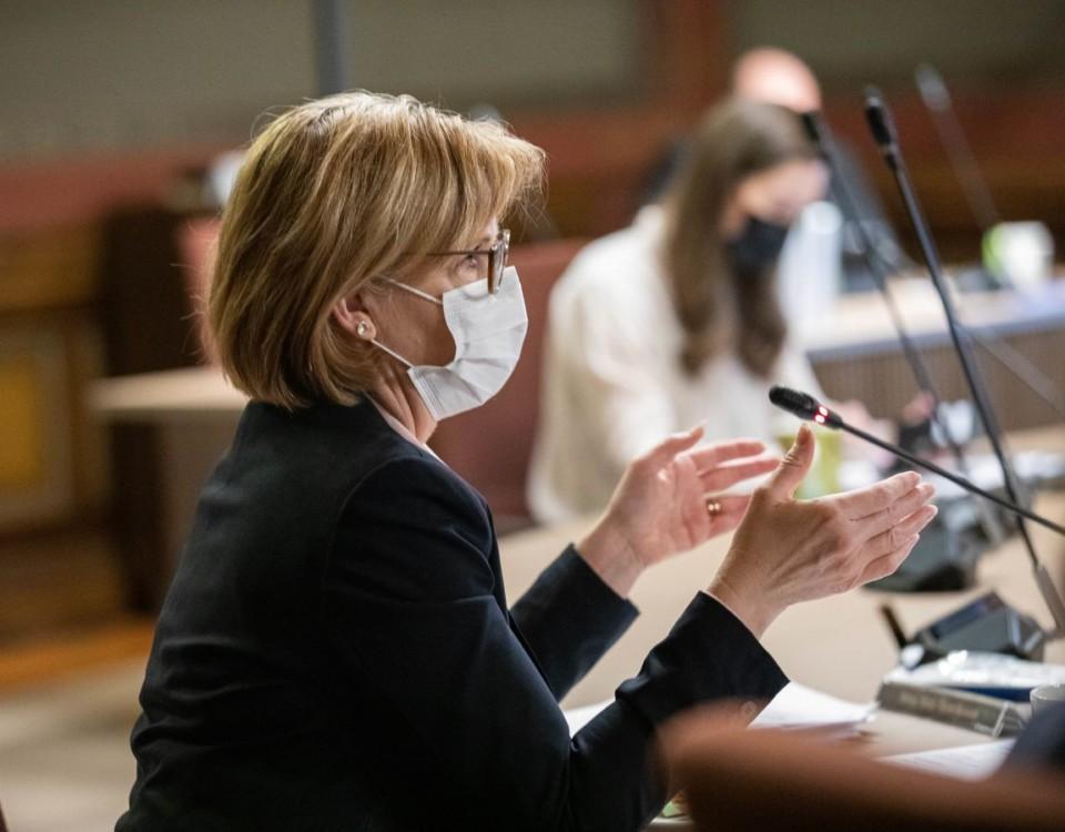 Kvinna med munskydd sitter vid förhandlingsbord