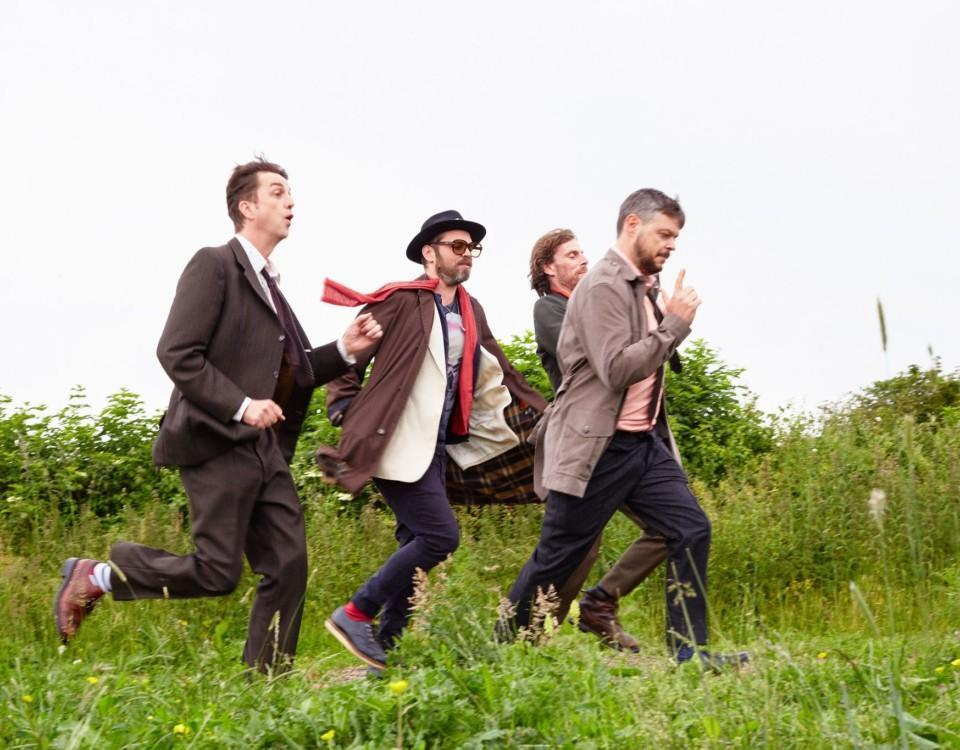 tre män springer i högt gräs