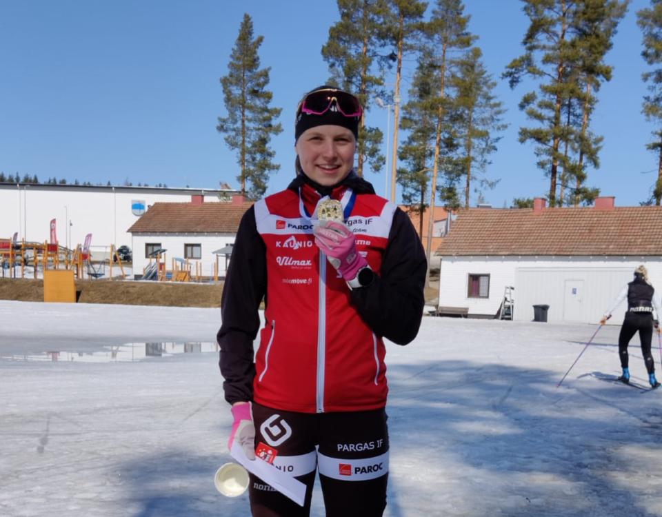 flicka poserar med medalj, det är snö omrking henne