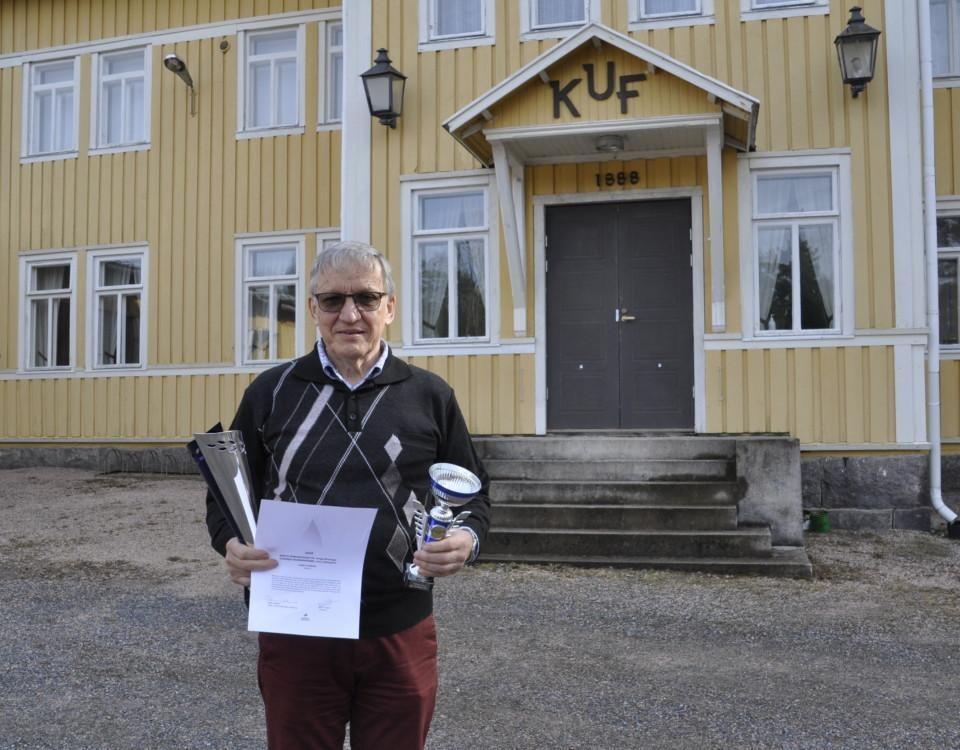 Äldre man med pokaler och diplom utanför ett föreningshus