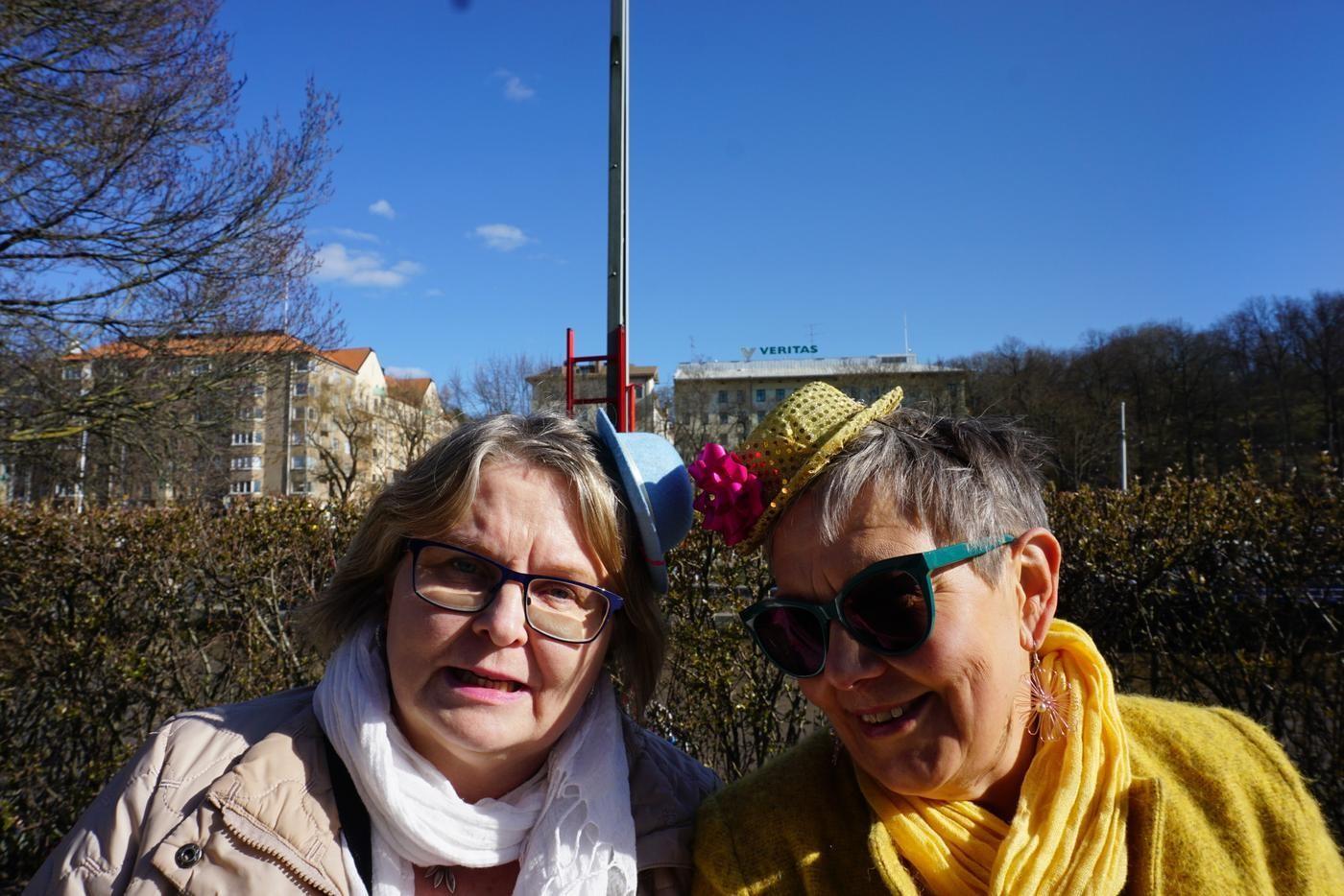 två glada kvinnor med små hattar på huvet