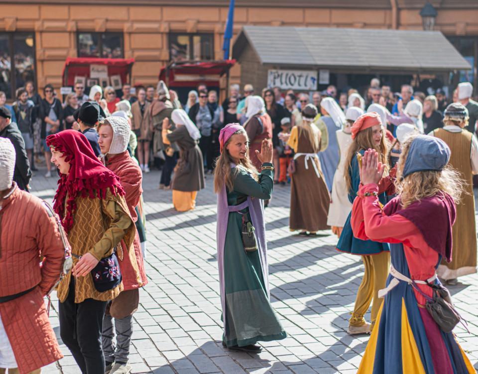 folksamling klädda i medeltidsutstyrsel dansar på torg