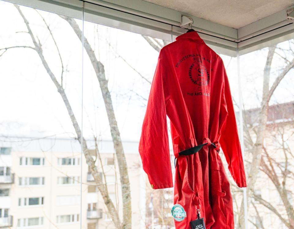 röd studentoverall hänger vid balkongfönster