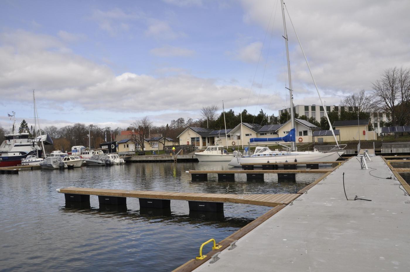 Brygga med båtplatser med bommar. i bakgrunden syns servicebyggnader