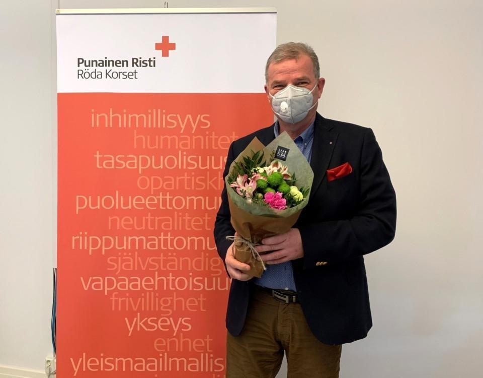 man ikkädd munskydd står och håller i en blombukett. han står framför Röda Kors-väg