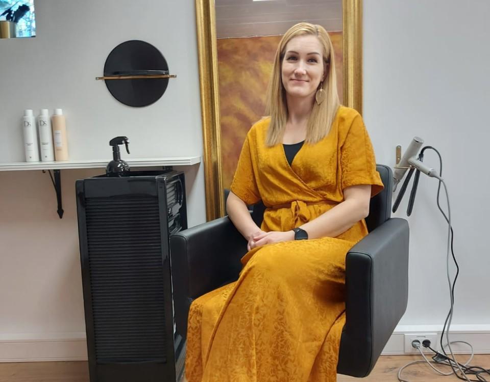 kvinna i orangegul klänning i en frisörstol