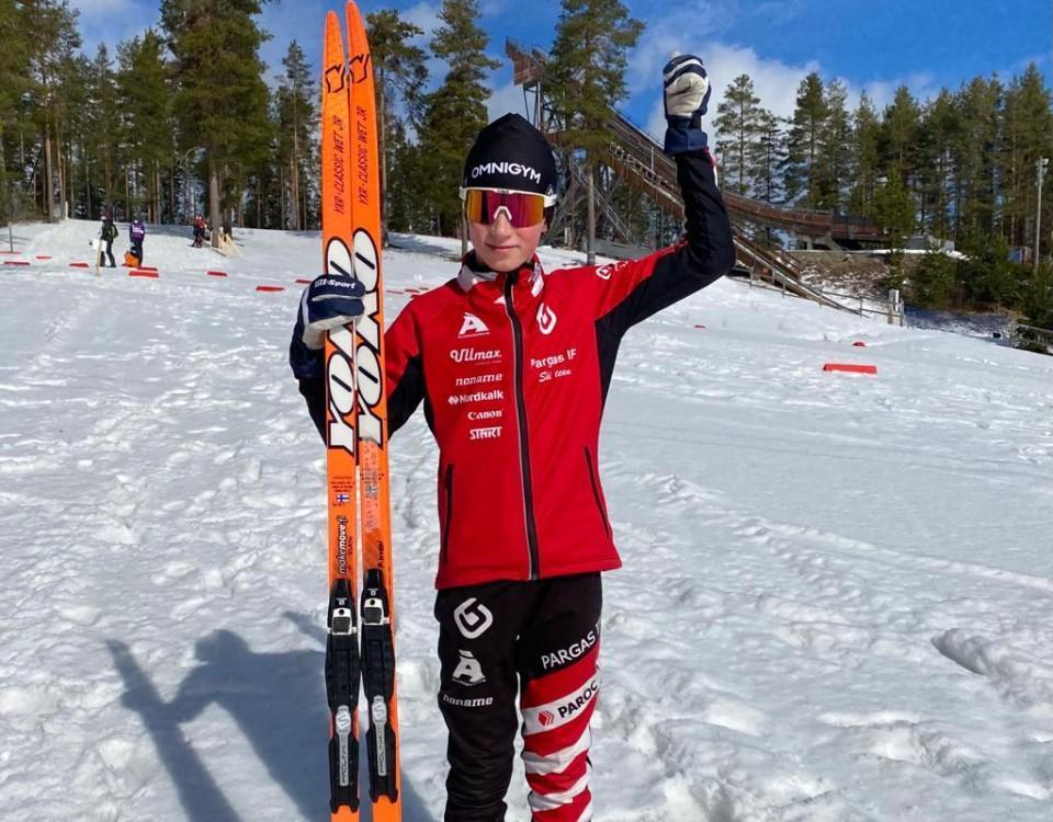 en skidåkare poserar med sina skidor i solen