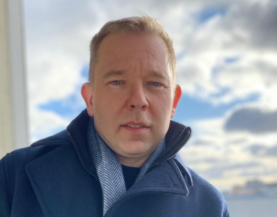 en man i blå jacka med en molnig himmel i bakgrunden