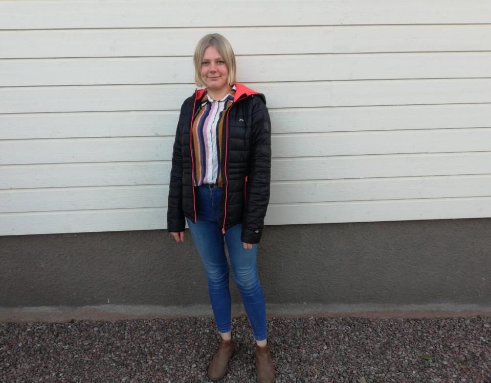 en ung kvinna står vid en vägg