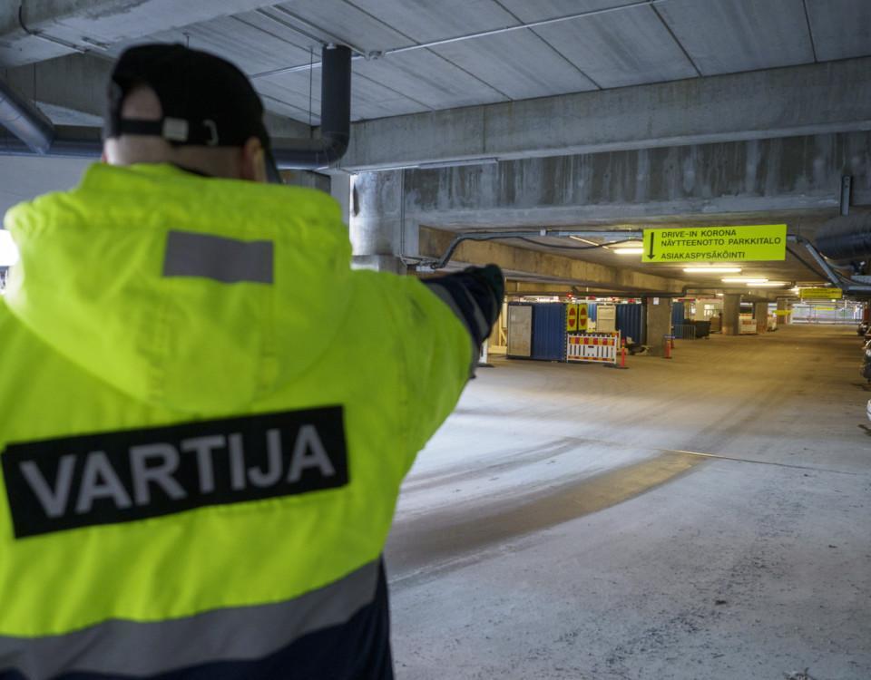 väktare dirigerar i riktning mot coronatest i parkeringshall