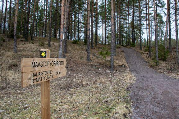 Träskylt som märker ut terrängcyklingsrutten pekar in mot stig i skogen.