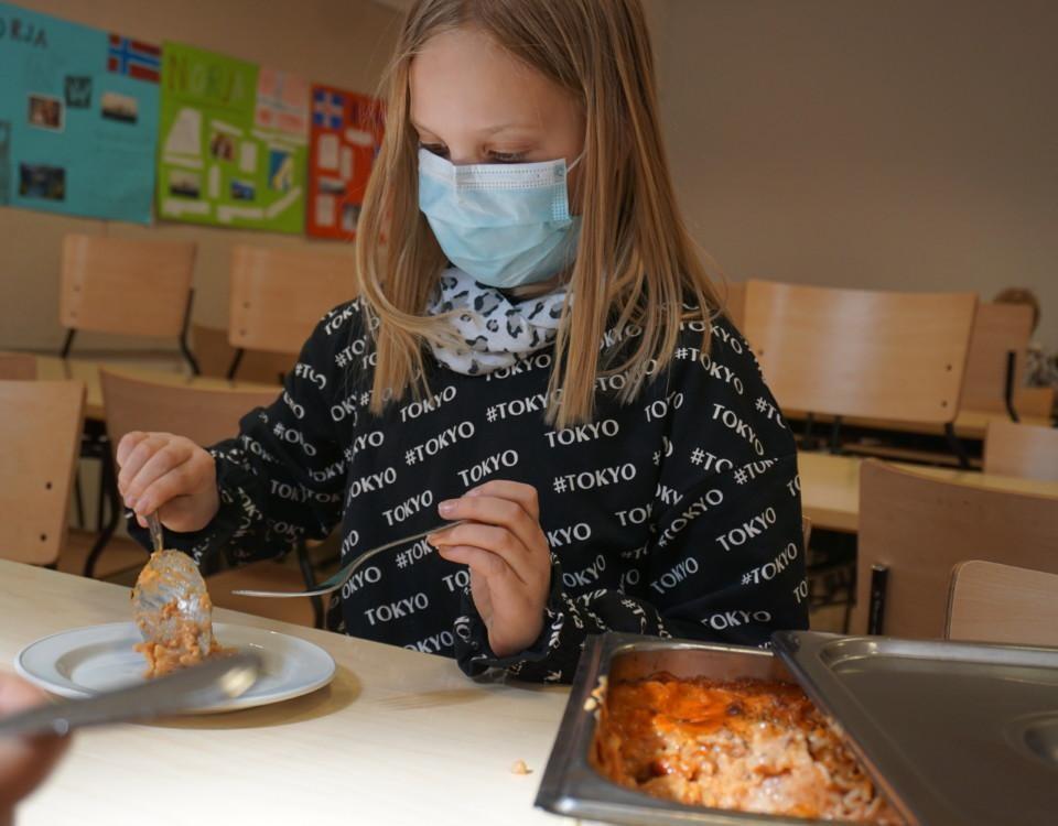 en flicka med munskydd lägger upp mat på sin tallrik