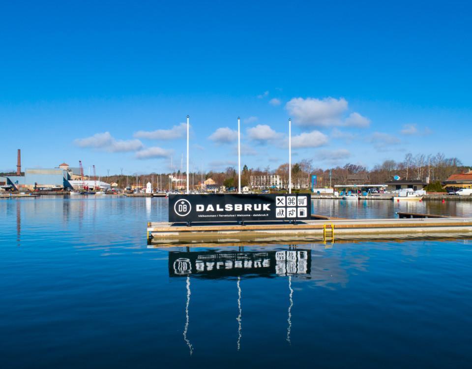 """Infarten sjövägen till en hamn. En stor skylt på bryggändan: """"Dalsbruk"""""""
