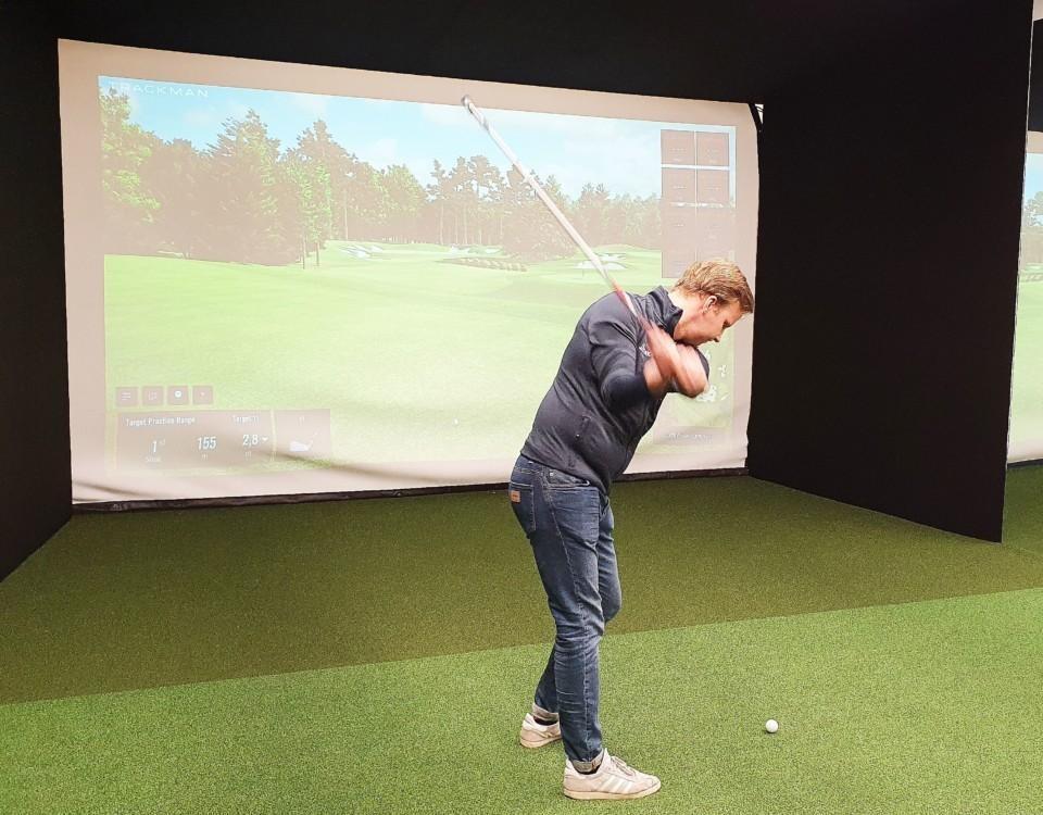 Man svingar golfklubba framför en projektorskärm.