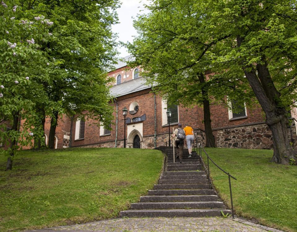 åbo domkyrka med gröna träd omkring och två personer på väg upp för en trappa
