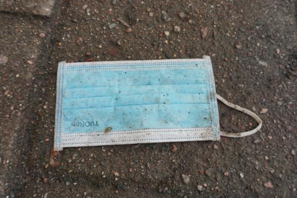 ett smutsigt munskydd ligger på gatan