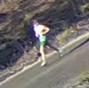 en suddig bild på en joggande man i gröna shorts och vit blus