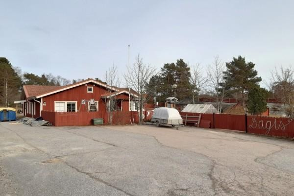 en röd daghemsbyggnad i trä fotograferad på avstånd