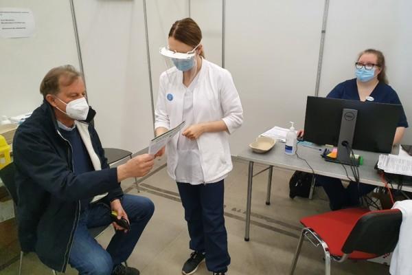 man sitter och kvinna i sköterskedräkt visar ett papper för honom