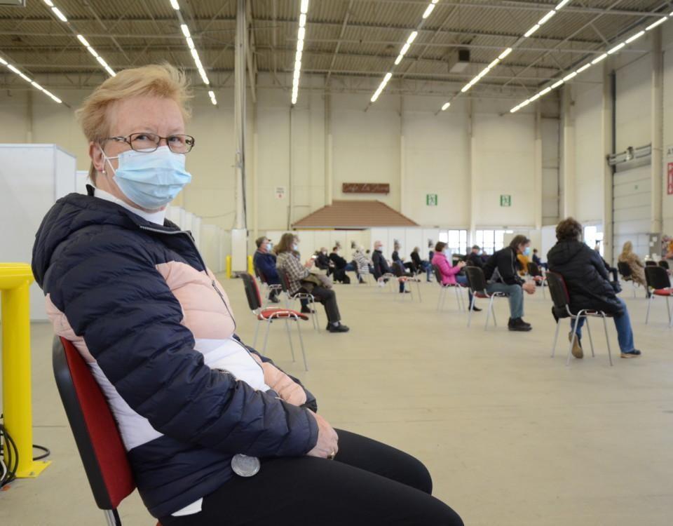 kvinna iklädd ytterrock o munskydd sitter på en stol, i bakgrundne ses många människor sitta på avstånd från varandra