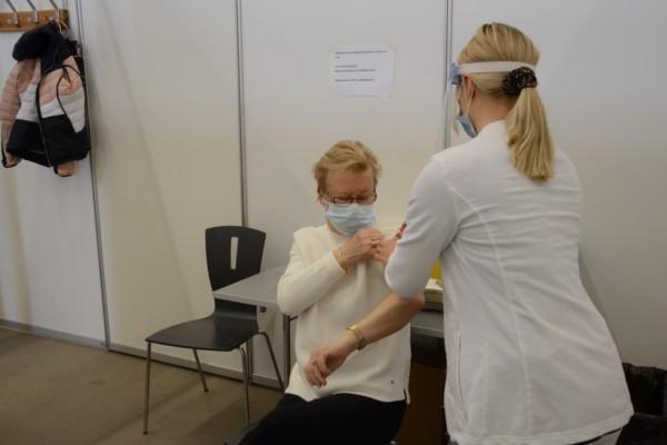 kvinna sitter på en stol och sköterska putsar hennes arm för vaccin