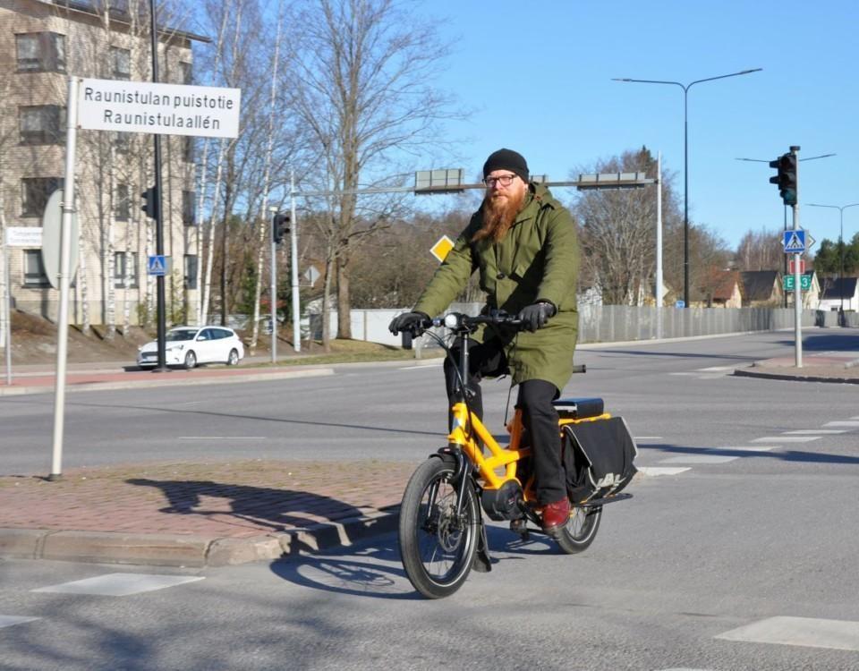 Skäggig man cyklar över övergångsställe