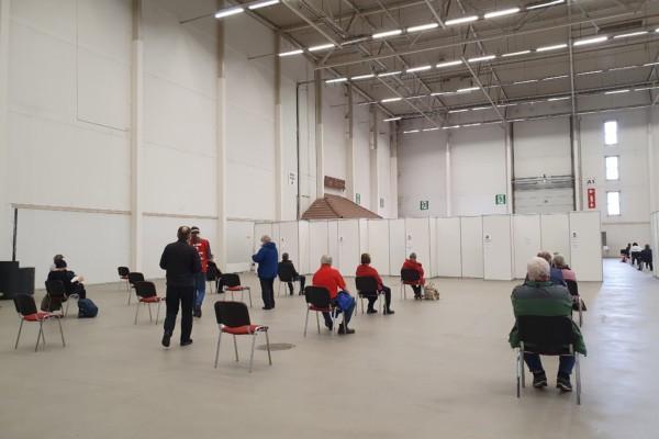 människor sitter utspridda på stolar i en mässhall