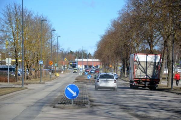 En väg med en massa trafikmärken och trafik