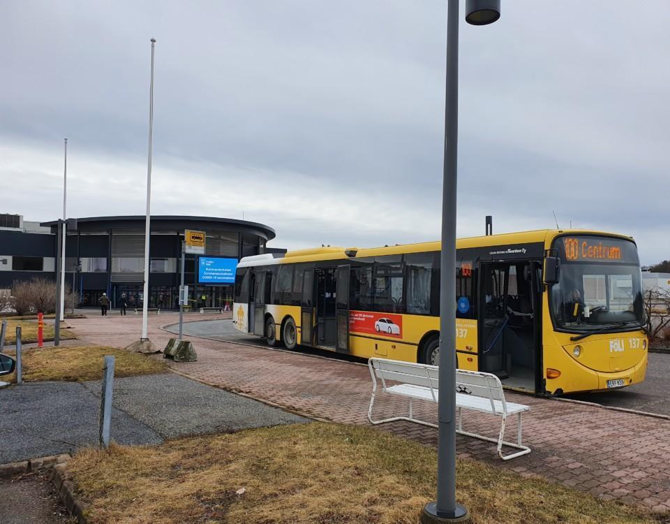 gul buss parkerad framför stor byggnad