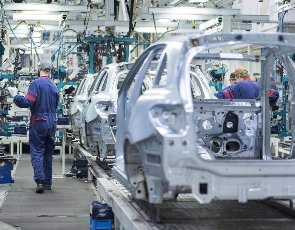 en produktionslinje med halvfärdiga bilar