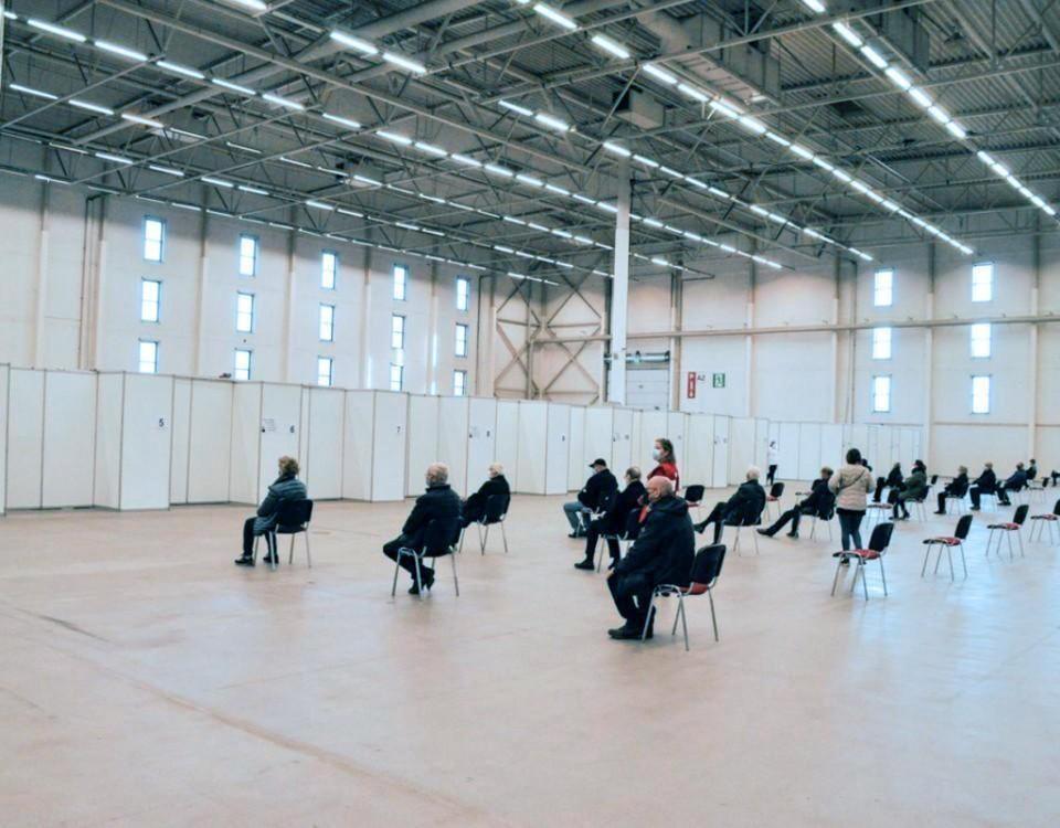 Stor hall med folk som sitter på stolar i väntan på vaccinering