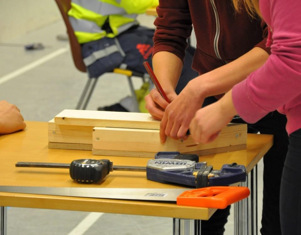 verktyg på ett bord och en massa händer