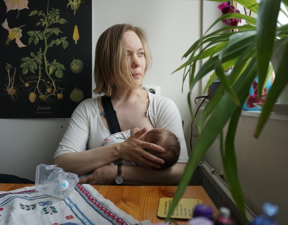 en kvinna ammar ett barn vid köksbordet och tittar rofyllt ut genom fönstret