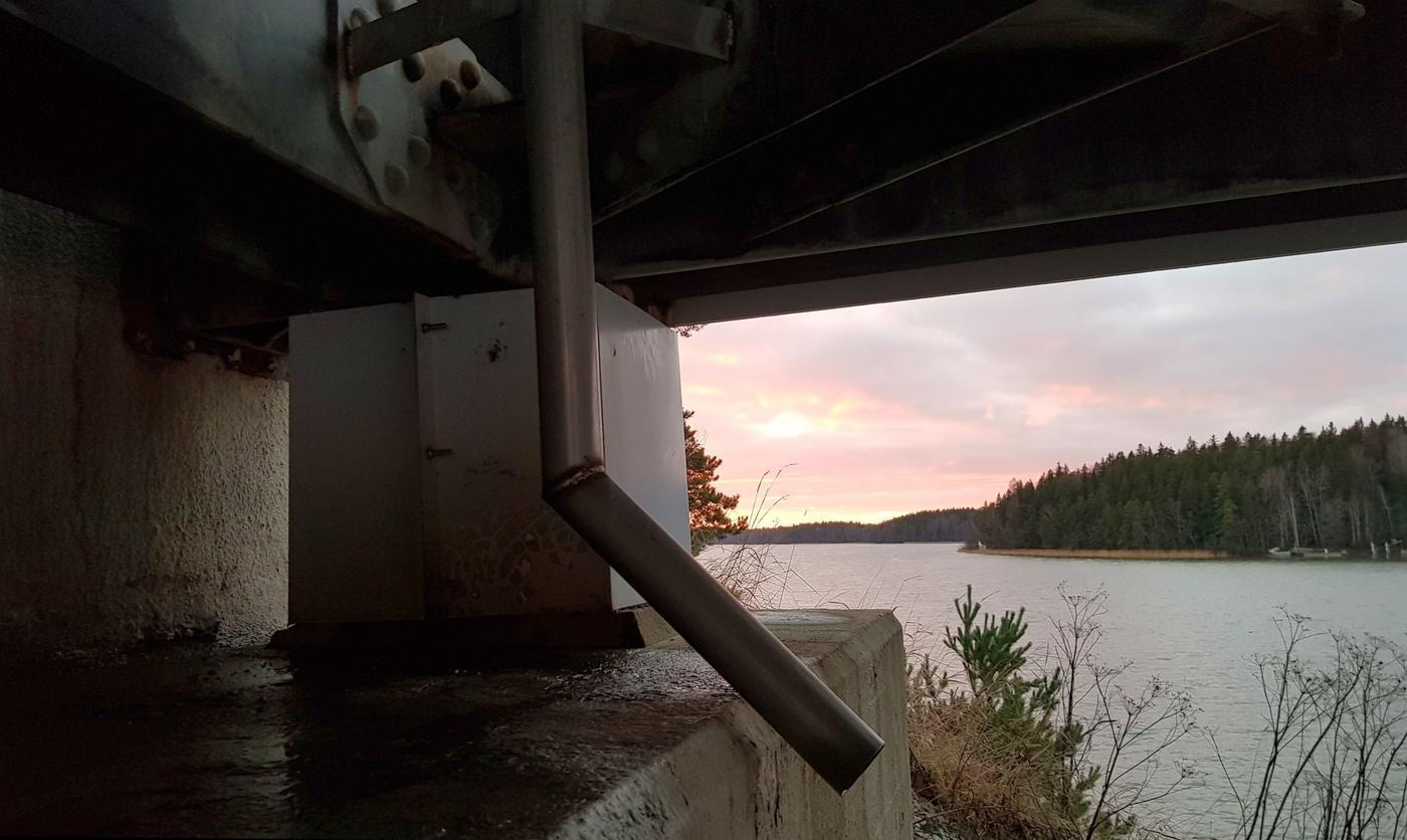 en solnedgång sedd från under en bro