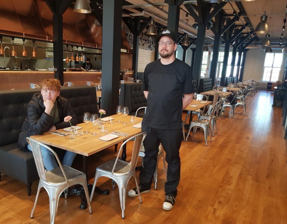 två killar i en restaurang med brunt golv