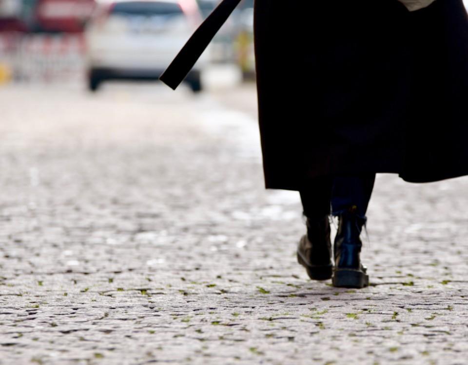 Person i svart kappa på en gata.