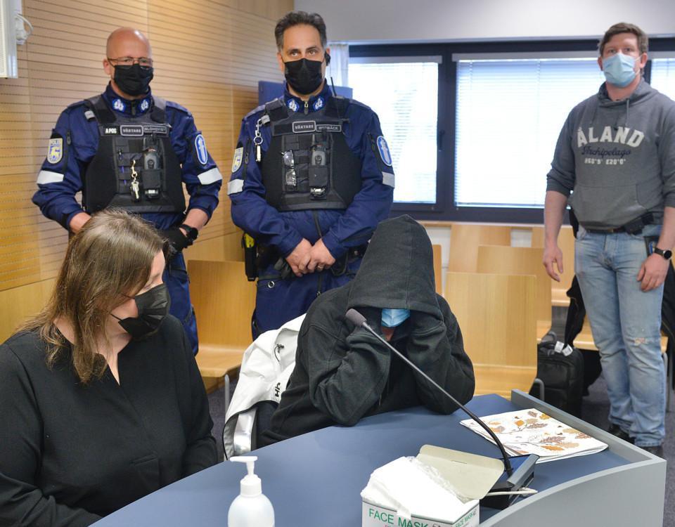 Två kvinnnor döljer sina ansikten på en rättegång
