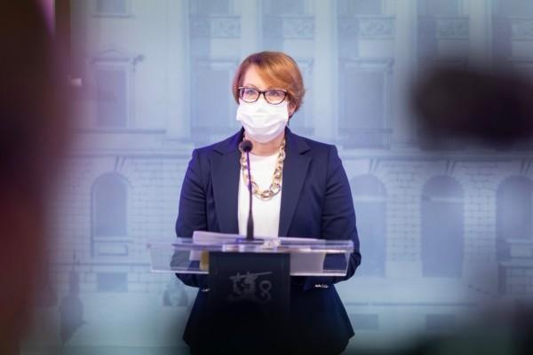 en kvinna med munskydd på ett presspodium