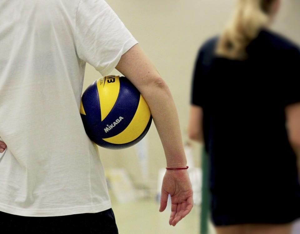 en ung person står med en volleyboll under armen
