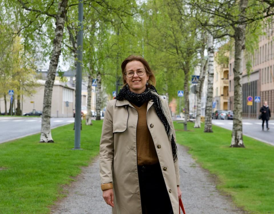 kvinna står på en grusväg omringad av grönskande björkar